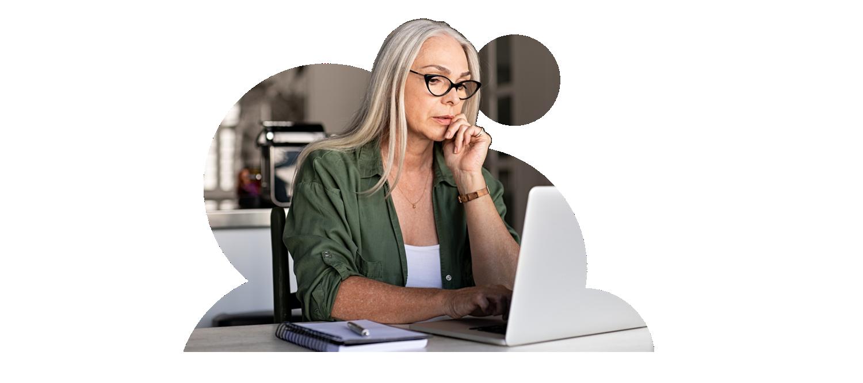 ノート PC の画面を見ている眼鏡を着用した女性の写真