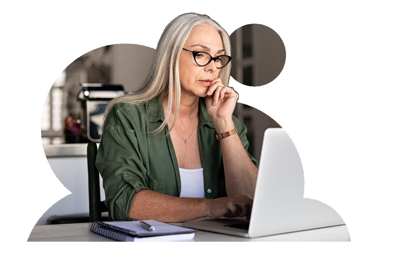 Afbeelding van vrouw met bril die op een laptop kijkt.